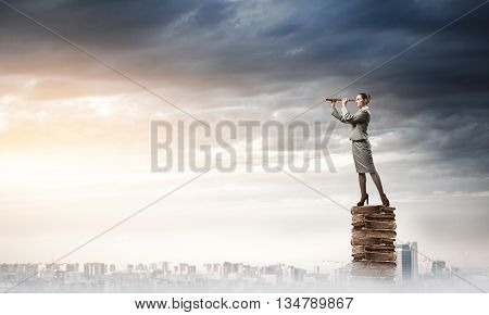 Career woman on pile of books looking in spyglass over city