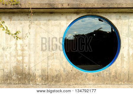 Round window on concrete wall with scum