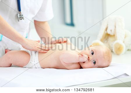a Doctor pediatrician examines the baby tummy