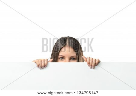 Business woman peeping from behind a white canvas, isolated on white background. Smart staff. Success and development. Business staff. Office clothes. Dress code. Presentable appearance.