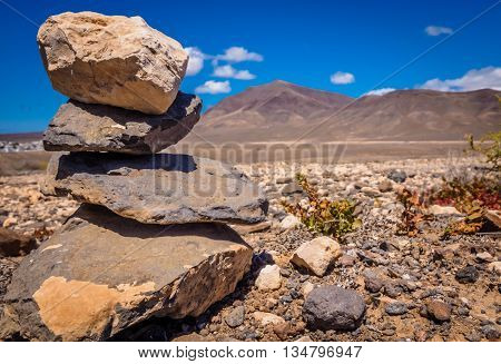 Pile of stones on the ground with the Pico de Redondo volcano and the landscape of southern Lanzarote in the background, Canary Islands, Spain