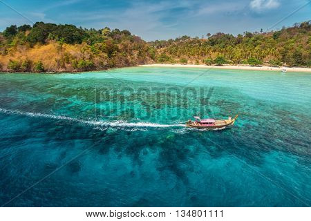 View of the island in Andaman sea with traditional long tail boats in a clear water, Thailand