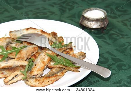 fried smelts Baltic fish on a dish on the tablecloth
