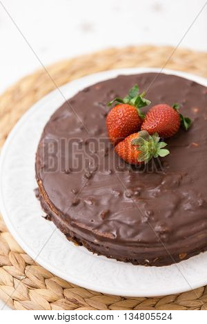 Homemade dark chocolate cake decorated with cocoa and fresh organic strawberries on top served on a white plate and straw tablemat.