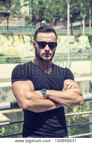 Handsome Muscular Hunk Man Outdoor in City Setting. Showing Healthy Body While Looking at Camera