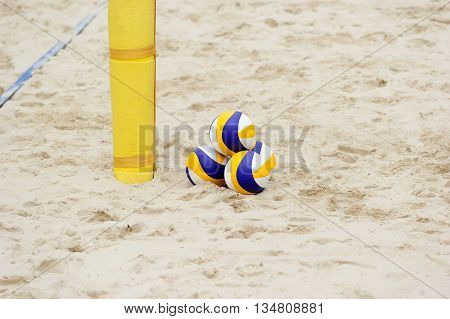 Volleyballbeach is a stack of three volleyballs sitting in the sand all ready and waiting for tournament play.