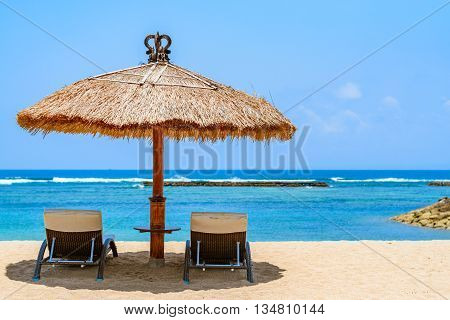 A beach hut with lounge chairs over looking a beautiful tropical beach on a perfect day.