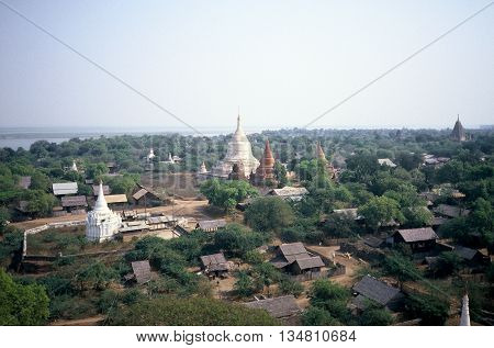 A view of some of the ancient ruins and Buddhist temples of Pagan, Burma (now called Myanmar), the village of Pagan, and the Irrawaddy River, as seen from atop the Gawdawpalin Buddhist Temple, circa 1987.