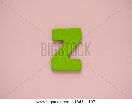 Capital letter Z. Green letter Z from wood on pink background.