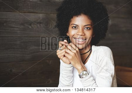 Close Up Shot Of Attractive Happy Cheerful Dark-skinned Young Woman Looking And Smiling At The Camer