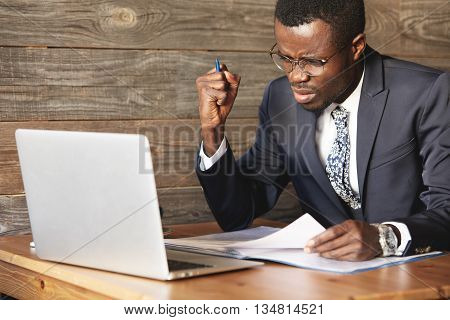 Angry African Businessman Is Displeased With Inefficiency In Digital Data. Irritated Shot Of Man In