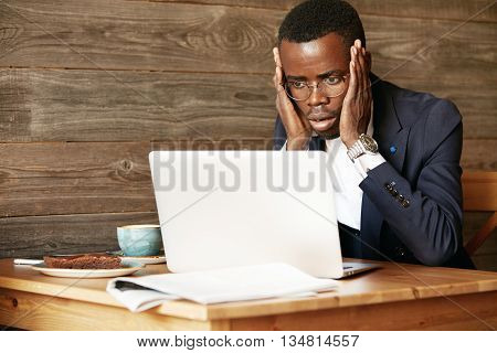 Handsome African Corporate Worker In Glasses Using Laptop For Distant Work, Sitting At The Hotel Lob