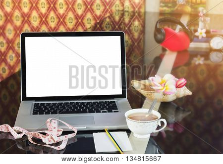 Blank screen computer notebook or laptop on counter with cup of hot tea in background of tape measure blank note paper or memo note and pencil for concept of searching media or data tips for weight loss and diet for health