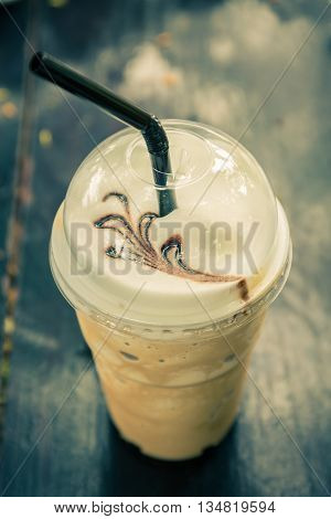 Iced blended frappucino in plastic cup on wood background. Iced coffee. Vintage color tone.