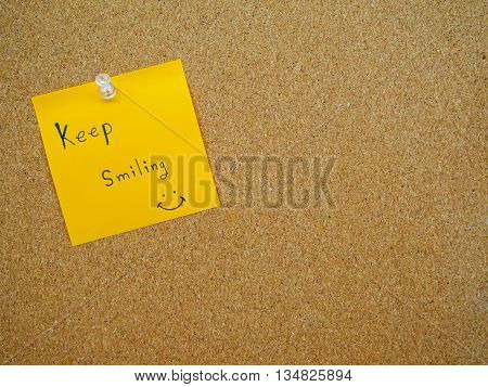 Keep smiling in post note on wooden board with copy space