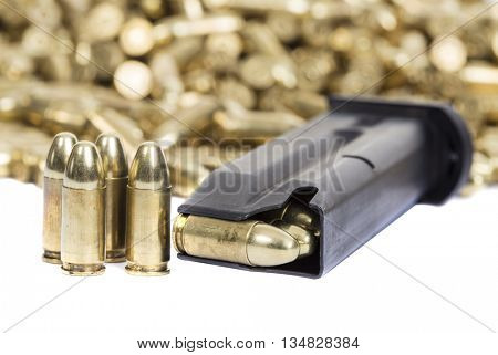 A loaded gun clip with a pile of bullets in the background