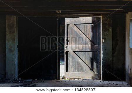 Open door of a dilapidated barn. It is dark in the barn and outside it is a sunny summer day.