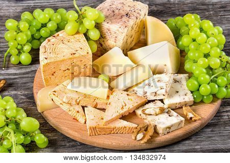 Cheese plate: organic homemade goat cheese with walnuts and spices. Green Grapes and walnuts on an old rustic background studio lights close-up