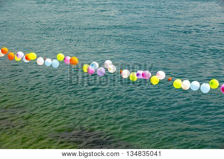 colorful balloons on the water are placed in a row