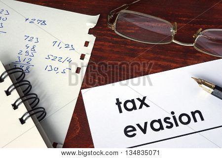 Tax evasion written on a paper. Financial concept.