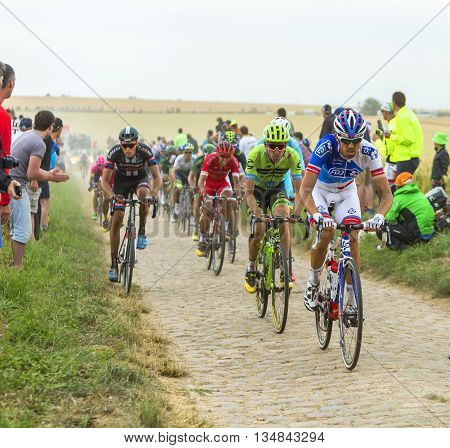 Quievy, France - July 07 2015: The peloton riding on a cobblestone road during the stage 4 of Le Tour de France 2015 in Quievy France on 07 July 2015.