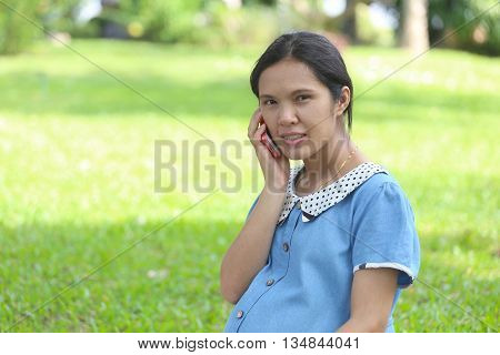 Asian pregnant women using smartphones call to doctor and query about in health care in the public park.