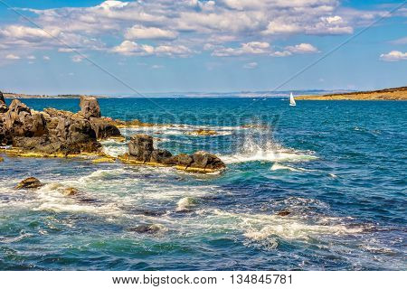 Small Boat In The Sea Near Rocky Shore