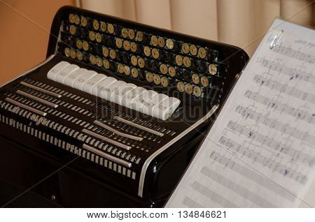 Old accordion and near it disclosed musical notations