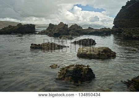 Dark Sullen Beach with Coral Rocks and Cloudy Sky