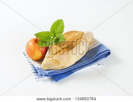 diamond shaped ciabatta bread and fresh apple on striped dishtowel