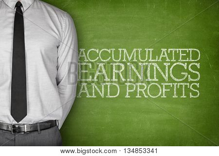 Accumulated earnings and profits text on blackboard with businessman standing side