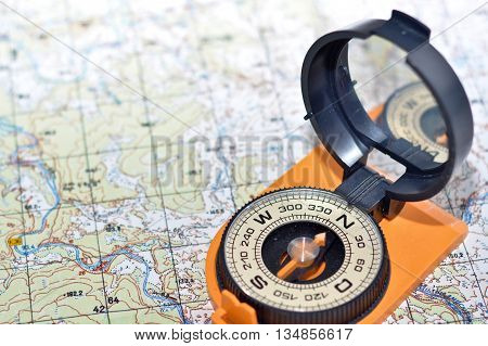 Compass & map - friends travelers. Magnetic compass on a topographic map.