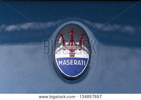 TURIN, ITALY - JUNE 13, 2015: Maserati logo on the hood of a MC12 model
