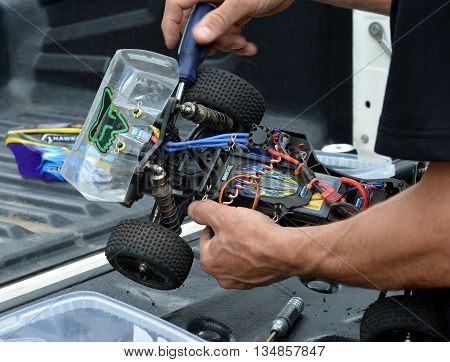 Sydney, Australia - December 14, 2014. Man working on the radio controlled buggy car model, internal combustion engine. (St Ives Showground, Sydney, Australia)