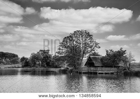 Stunning Black And White Landscape Image Of Boathouse On Lake In Summer