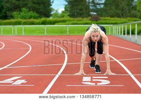 Athletic Woman In The Starter Position On A Track