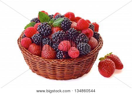 Basket vith blackberries, strawberries and raspberries isolated on white background