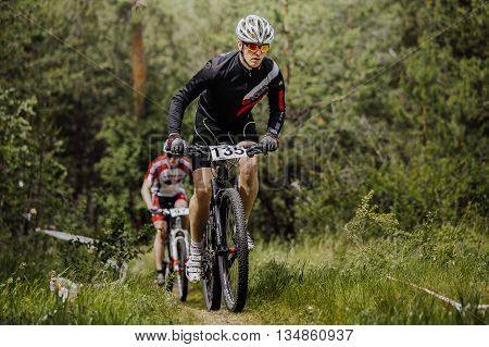Chelyabinsk Russia - June 5 2016: two men athletes cyclist going uphill in woods during cross-country race
