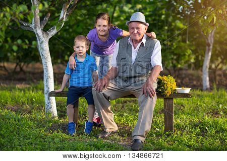 Grandfather with grandchildren sitting on a bench in the orchard