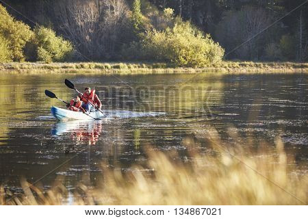 Father and son kayaking together on a lake, front view