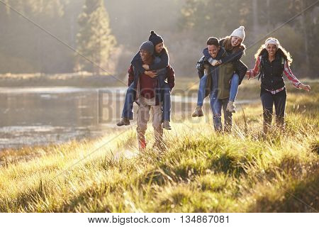 Group of friends have fun piggybacking by a lake