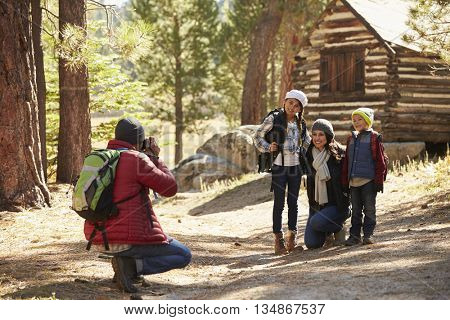 Family taking a photo in front of a log cabin in a forest