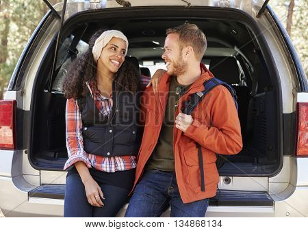 Couple at the open back car before a hike look at each other