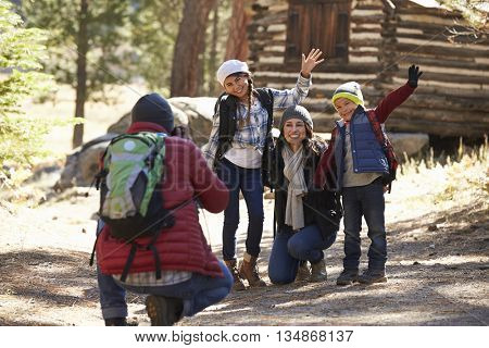 Family taking a photo in front of a log cabin, close up