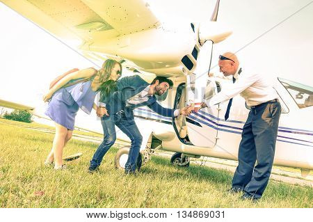 Young couple getting on lightweight airplane with captain welcome - People boarding on excursion plane - Alternative adventure vacation concept - Vintage filter with sunflare halo and tilted horizon