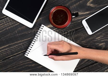 Hand Writes A Black Pen In A White Notepad