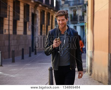 Young man listening music with smartphone earphones walking in the street