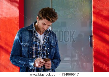 Young man using smartphone outdoor with jeans