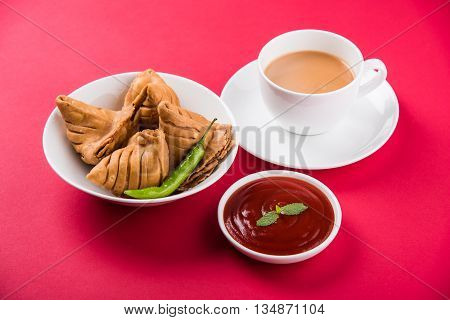 Samosa snack with tomato ketchup and hot tea, Fresh samosas with ketchup and hot chai ready for breakfast