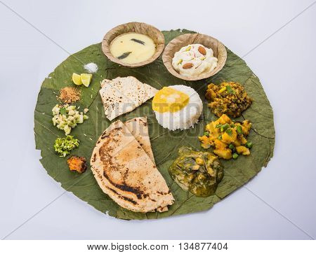 typical maharashtrian food served in plate and bowls made of leaf includes kadhi and shrikhand, plain dal, spinach curry, aalu mutter, plain rice, papad, bhakri or bhakar or roti and variety of salad